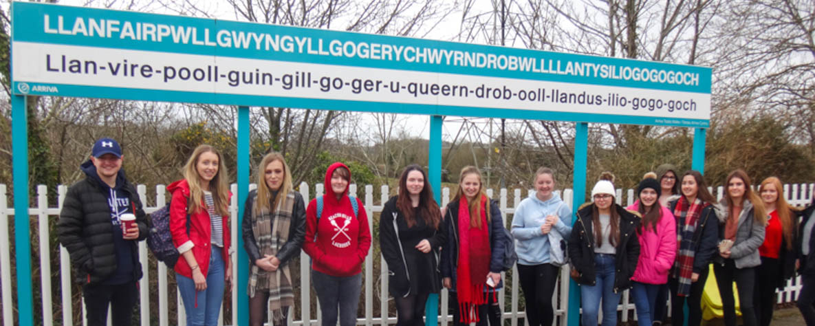 Group of Coleg Gwent AS Welsh students, with iconic Welsh town signage.