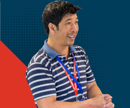 tutor standing in front of dark blue and red background