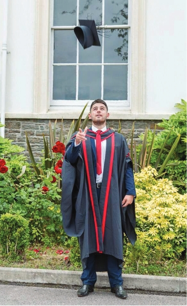 male student in graduation gown throwing his hat