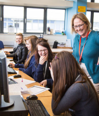 staff member laughing with multiple students sat at computers