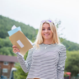 female student outside holing her results with greenery background