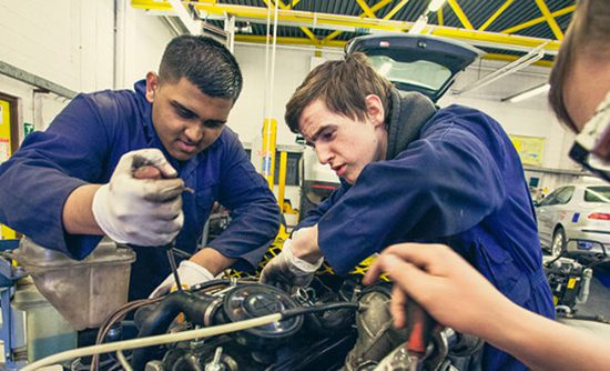 2 students working on a car engine