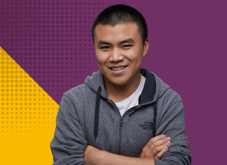 Student in front of Purple/yellow triangle background