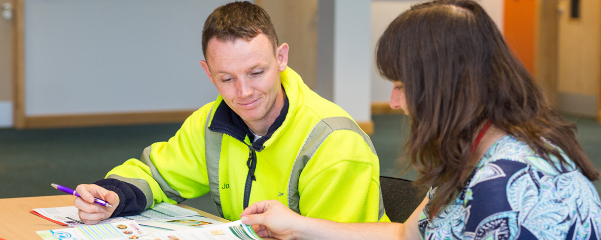 staff member sat at desk helping male in hi vis jacket on