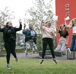 students celebrating outside campus