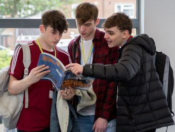 3 males looking at a book together in a library