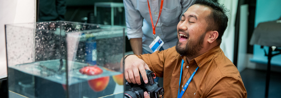 Photography student with camera laughing