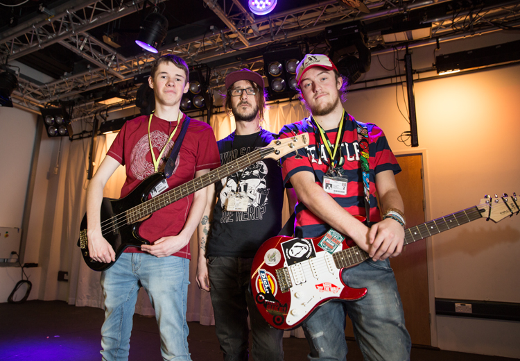 3 male musicians, 2 with guitars on a stage
