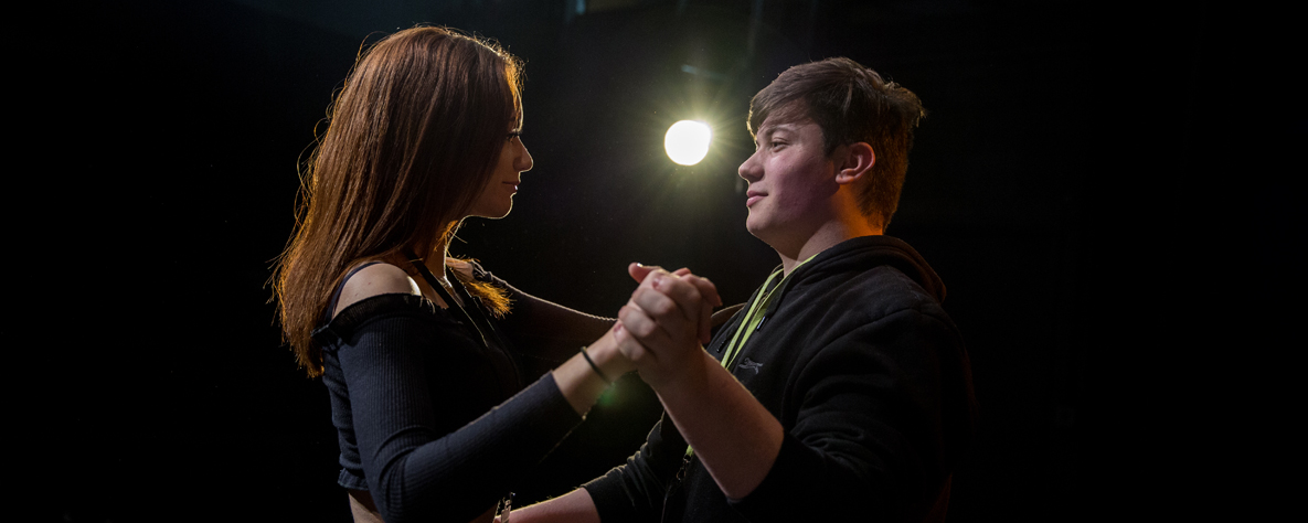 2 students performing with lighting in the background
