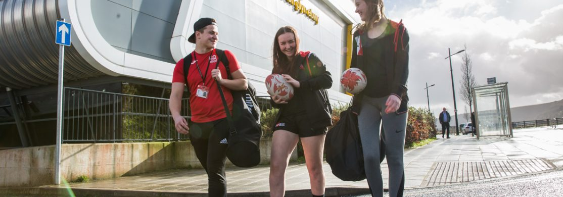 3 students holding rugby balls and sports kit in front of sports building