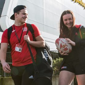 male and female student carry rugby ball and sports bags