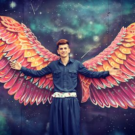 man stood in front of huge coloured wings painted on a wall