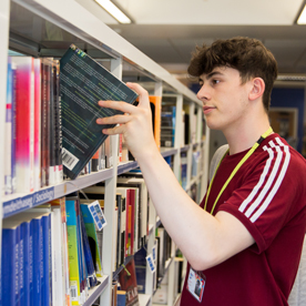 male student taking a book from a shelf in the library
