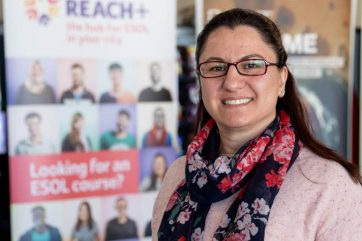 Woman standing in front of Reach+ banner