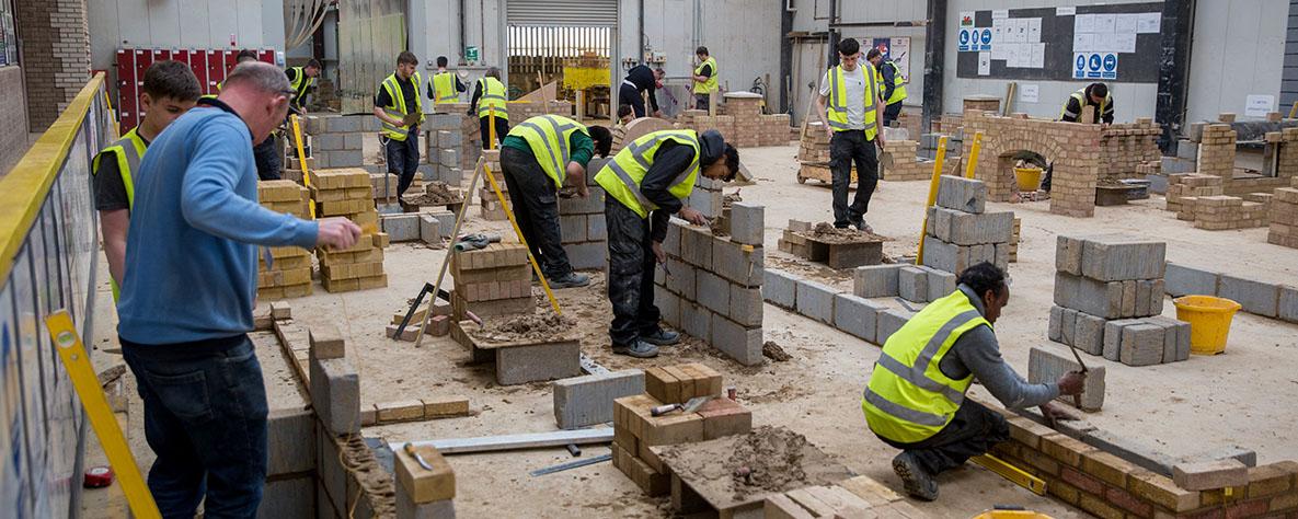 Learners in hi-viz laying bricks and blocks