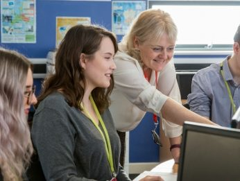 Students being supported by a tutor in the classroom