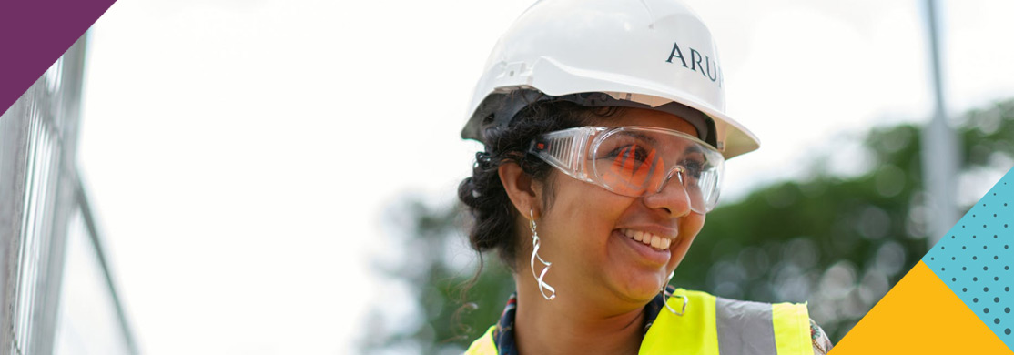 Woman in hard hat, hi-vis and safety glasses